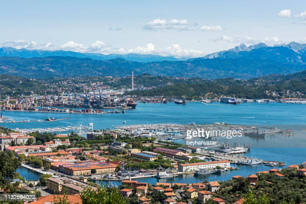view of the military, commercial dock and ships with mountains of la spezia in italy - la spezia stock pictures, royalty-free photos & images