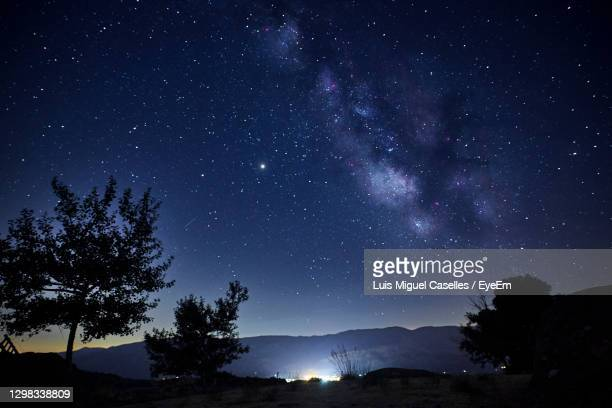 view of the milky way over the lights of a mountain village. concept science, astronomy - star shape stock pictures, royalty-free photos & images