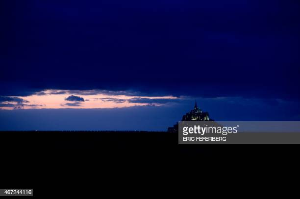 View of the Mont SaintMichel and its Gothic Benedictine abbey on March 21 2015 at sunset as driven by the effects of the solar eclipse on March 20...