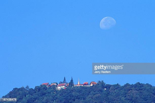 View of the moon setting behind Wat Doi Suthep atop Doi Suthep mountain on the western edge of Chiang Mai