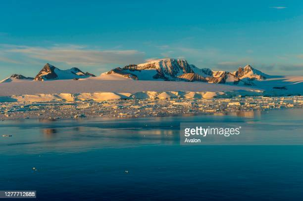 View of the mountains of Hope Bay on the tip of the Antarctic Peninsula from the Antarctic Sound with icebergs and ice floes in the foreground.