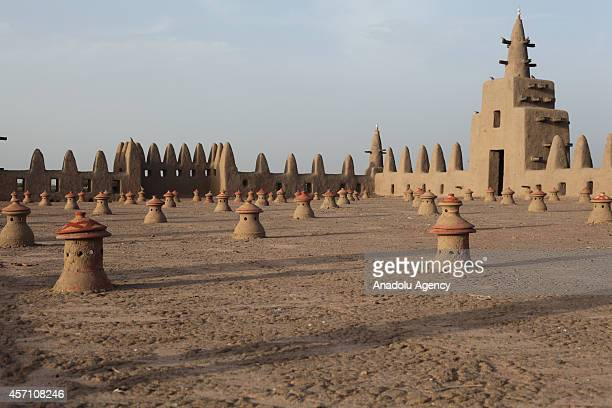 A view of the mud mosque and its palm sticks are seen in Djenne Mali on October 6 2014 The Great Mosque of Djenne is the largest mud brick building...
