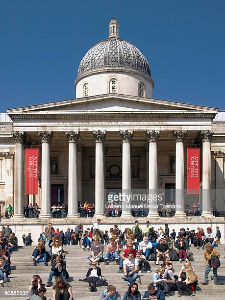 View of the National Portrait Gallery in Trafalgar square with a lot of tourists crowed the place in a sunny day.