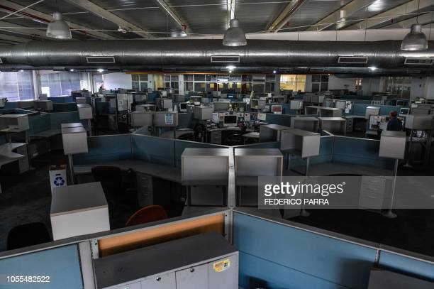 View of the newsroom of Venezuelan newspaper El Nacional in Caracas on October 5 2018 Surrounded by empty chairs a bunch of journalists try to keep...