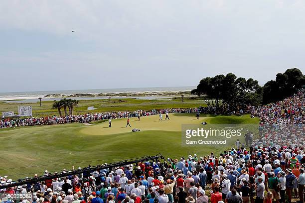 View of the ninth green as Rory McIlroy of Northern Ireland, Carl Pettersson of Sweden and Bo Van Pelt of the United States prepare to putt during...