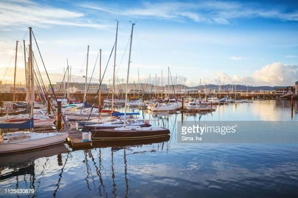 Blick auf den alten Hafen von Gijon und Yachten bei Sonnenuntergang, Spanien