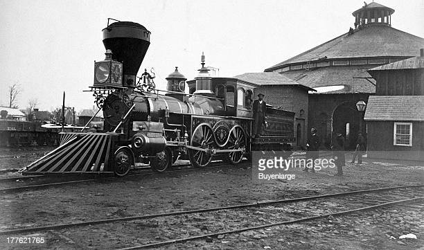 View of the ornately decorated locomotive J.H. Devereux, of the United States Military Railroad, with two crew members on board outside the...