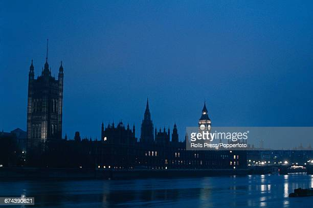 1970 view of the Palace of Westminster at night with the Elizabeth Tower containing Big Ben on the right and Victoria Tower on the left located...