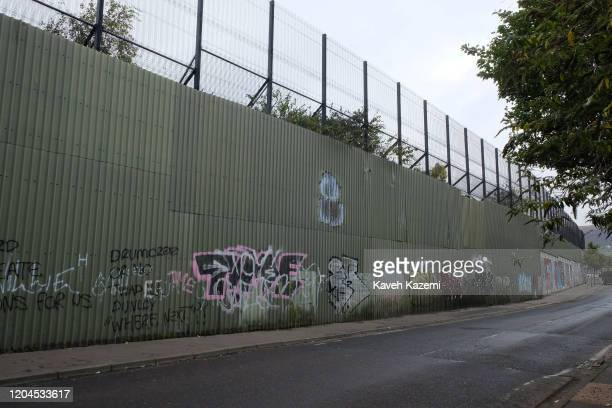 A view of the peace wall with the high wall and fences of the Catholic side of the Cupar Way which runs between the peace line dividing the...