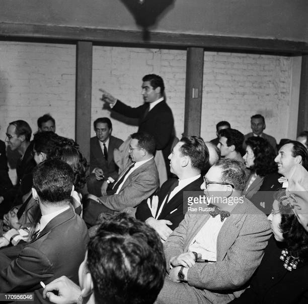 View of the photographer Robert Capa standing in the middle of a meeting of the American Society of Media Photographers New York 1948