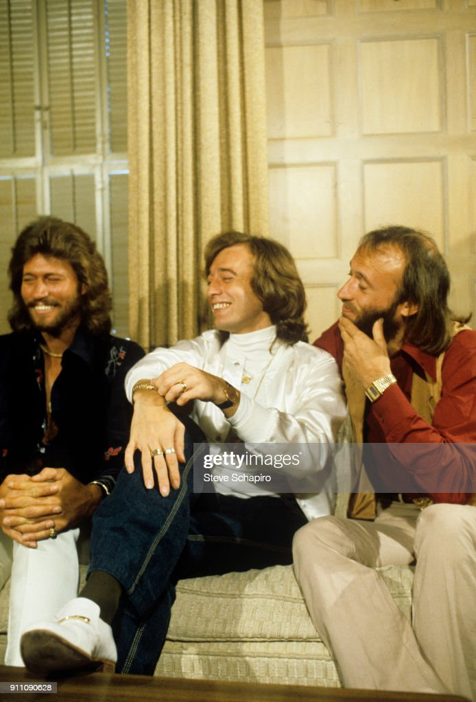 View of the pop group the Bee Gees, from left, Barry Gibb, Robin Gibb (1949 - 2012), and Maurice Gibb (1949 - 2003), as they share a laugh, seated on a couch, 1970s.