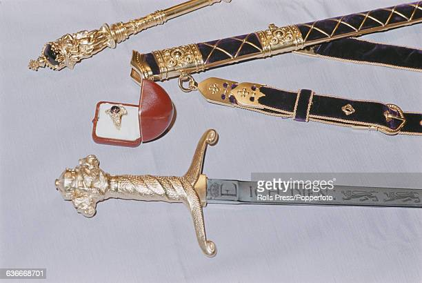 View of the Prince of Wales's ceremonial investiture sword etched with the motto 'Ich Dien' along with the velvet covered scabbard and belt, golden...