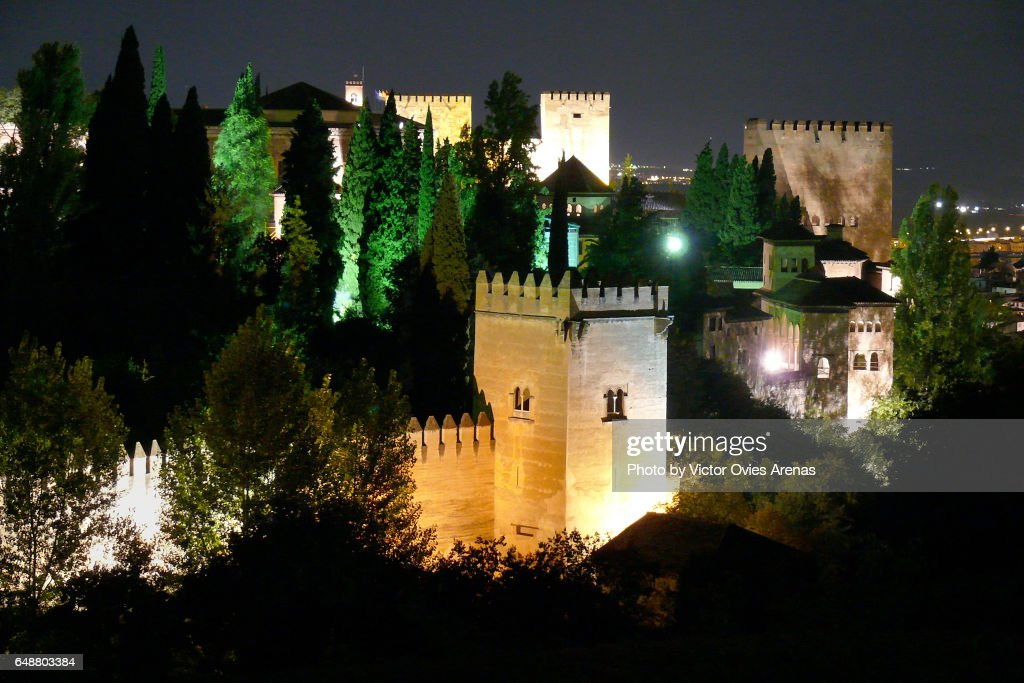 View of the ramparts and towers of the Nasrid Palaces in the Alhambra illuminated at night from Cerro del Sol in Granada, Andalusia, Spain : Foto de stock