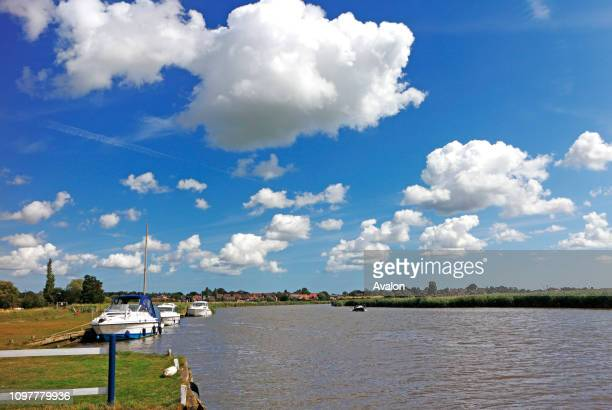 A view of the River Yare with moored boats by Reedham Ferry on the Norfolk Broads at Reedham Norfolk England United Kingdom