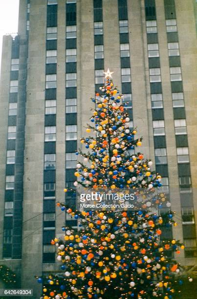 View of the Rockefeller Center Christmas tree fully adorned in colored globe lights and a 5pointed star in Rockefeller Center Plaza midtown Manhattan...