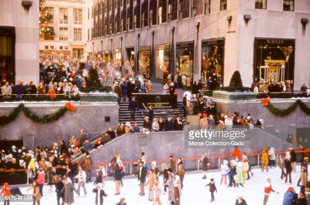 View of the Rockefeller Center ice rink filled with visitors skating during the Christmas season in Rockefeller Plaza midtown Manhattan New York City...