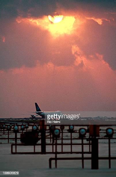 view of the runway of Ngurah Rai airport in Denpasar Bali at sunset with Garuda plane