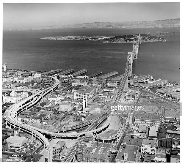 A view of the San FranciscoOakland Bay Bridge stretching for miles as the buildings streets and docks enclose the bridge before it extends over the...
