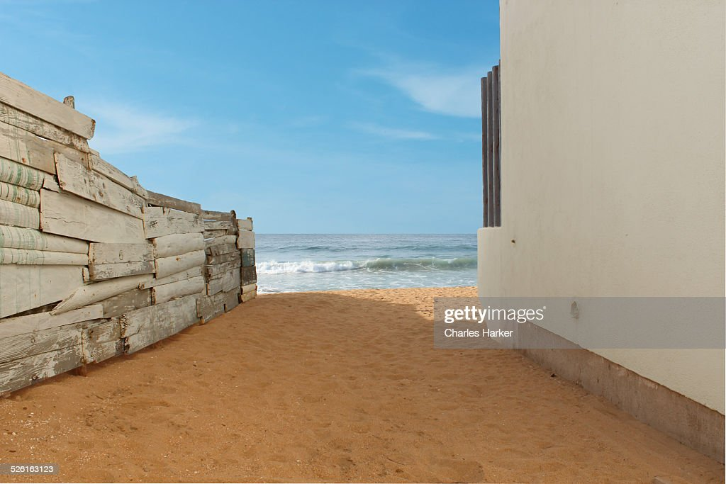 View of the Sea between a fence and building : Stock Photo