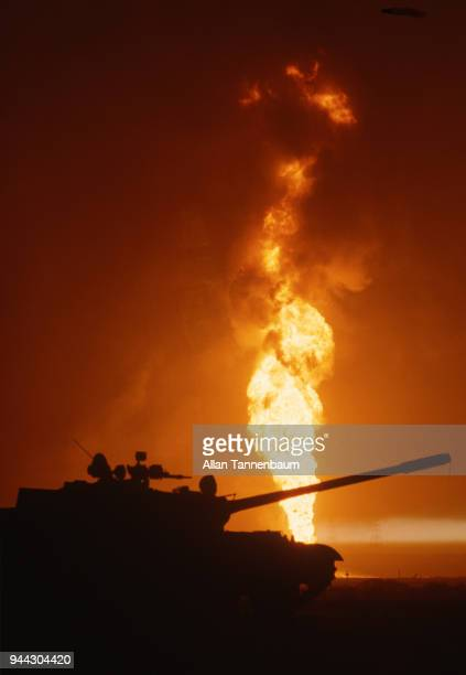 View of the silhouette of an American tank in front of a burning oil well Kuwait 1991