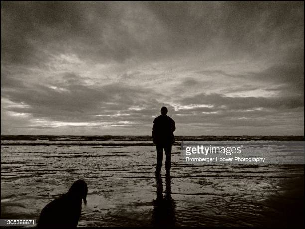 View of the silhouettes of a young woman and her dog, Nebo, at Ocean Shores Beach, Washington, 1991.