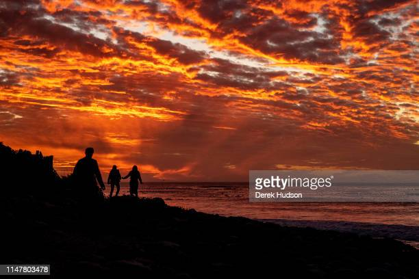 View of the silhouettes of beachgoers under the sunsetilluminated clouds on Long Beach Kommetjie Western Cape South Africa May 4 2019