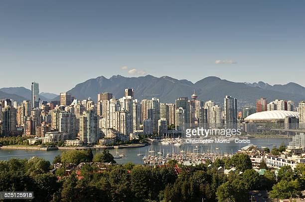 A view of the skyline of downtown Vancouver with False Creek in the foreground and the Coast mountains in the background with the sports venue BC...