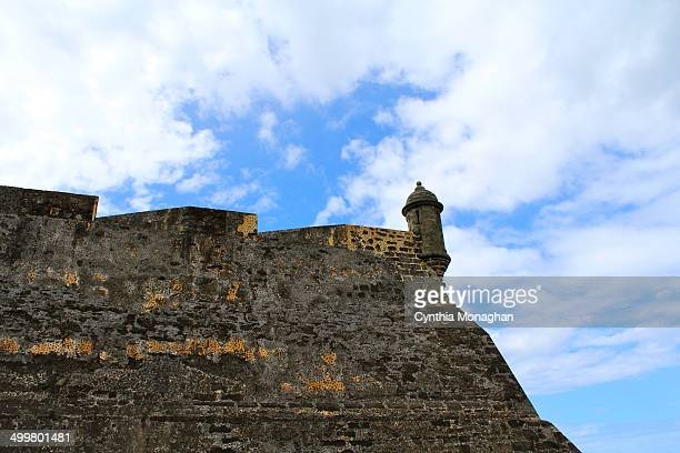 CONTENT] A view of the Spanish fort in San Juan Puerto Rico Old stone walls with a tower Beautiful blue sky with white swirling clouds