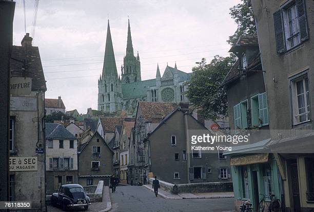 View of the spires of Cathedrale NotreDame de Chartres as they tower over a quiet street Chartres France June 1959