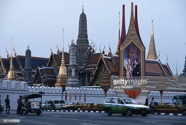 View of the spires of Wat Phra Kaew inside the Grand Palace, with a picture of the King and Queen of Thailand..