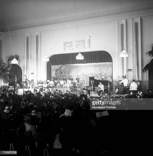 View of the stage of the Casinò di Sanremo where musicians are rehearsing the pieces of the IV Sanremo Music Festival; on the wall, over the curtain,...