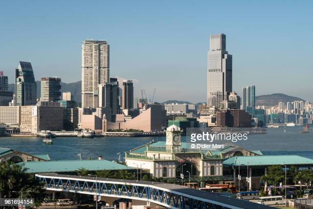 View of the Star Ferry terminal in Hong Kong island Central and the Tsim Sha Tsui skyline in Kowloon across the famous Victoria harbor