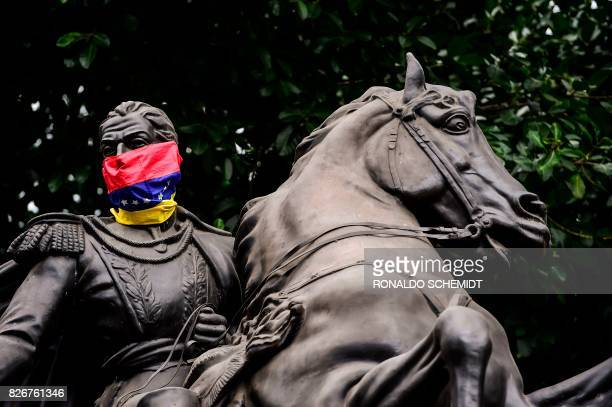 View of the statue of Venezuela's liberator Simon Bolivar with a Venezuelan national flag used as mask in Caracas on August 5 2017 / AFP PHOTO /...