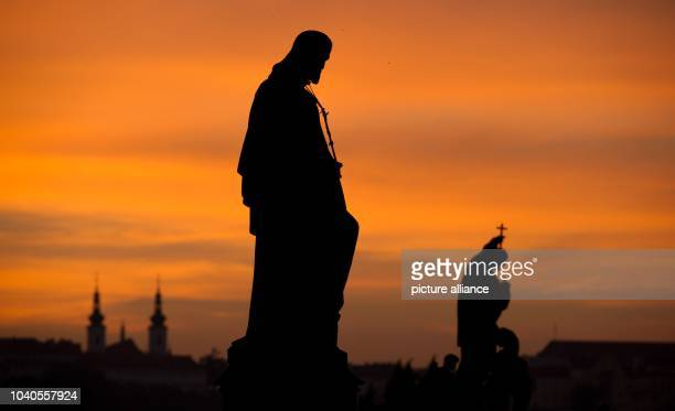 View of the StJoseph and St Francis Xavier stone sculptures on the Charles Bridge in Prague Czech Republic at sunset on 8 October 2013 Photo...