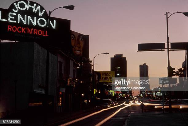 A view of the Sunset Strip looking west with billboards for John Lennon 'Rock 'N' Roll' Michael Jackson 'Forever Michael' Mac Davis 'Burnin' Thing'...