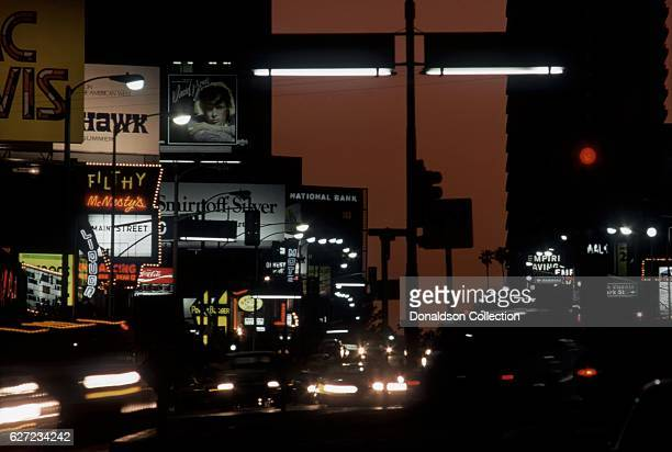 View of the Sunset Strip looking west with billboards for Mac Davis 'Burnin' Thing', David Bowie 'Young Americans' and the nightclub Filthy McNasty's...