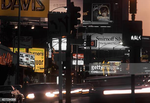 A view of the Sunset Strip looking west with billboards for Mac Davis 'Burnin' Thing' David Bowie 'Young Americans' and the nightclub Filthy...