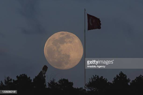 A view of the Super Pink Moon which is named for a pink wildflower and Turkish flag in Ankara Turkey on April 07 2020
