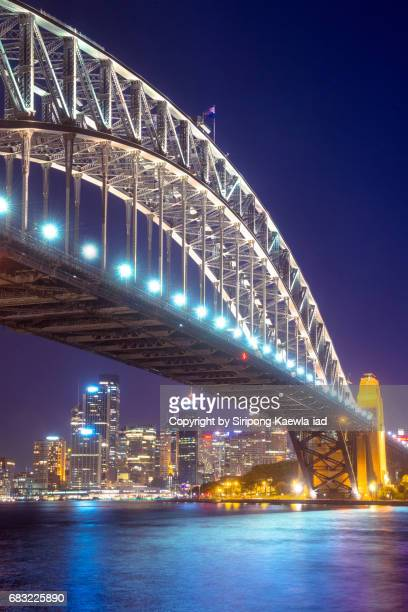 view of the sydney city under the harbour bridge in twilight time, australia. - international landmark stock pictures, royalty-free photos & images