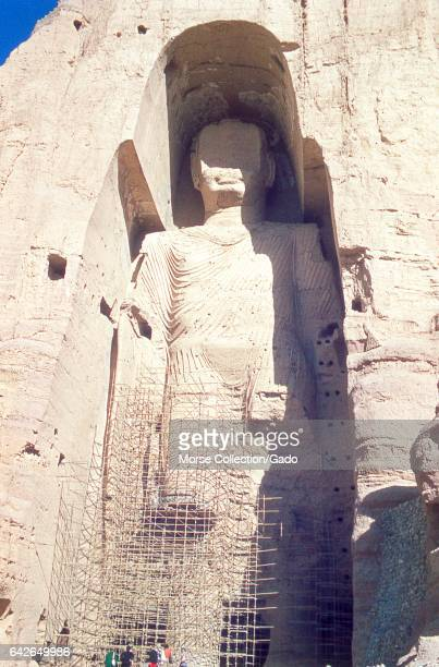 View of the taller Bamiyan Buddha statue known as Salsal standing in his giant niche November 1975 A group of tourists standing at the base are...