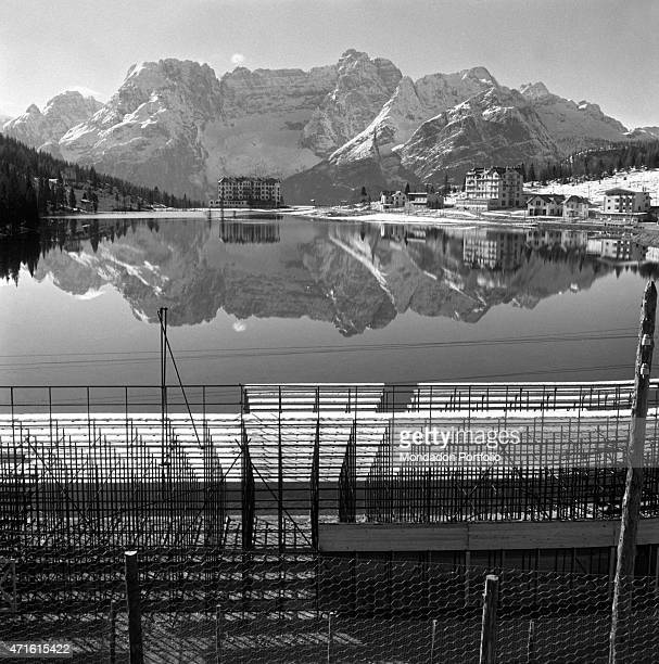 View of the terraces placed on the edge of the pond that will hold the ice rink for the VII Olympic Winter Games In the background the Dolomites...