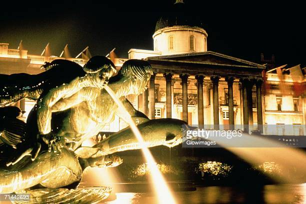 view of the trafalgar fountain statue at night, london, england - national gallery london stock pictures, royalty-free photos & images