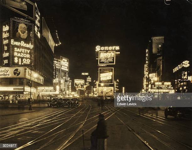 View of the traffic and illuminated advertisements in Times Square at night seen from 45th Street looking northward New York City