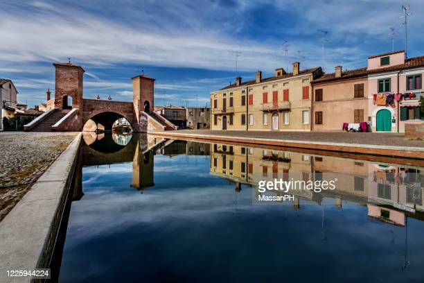 view of the trepponti bridge and canal in comacchio, italy - ferrara stock pictures, royalty-free photos & images