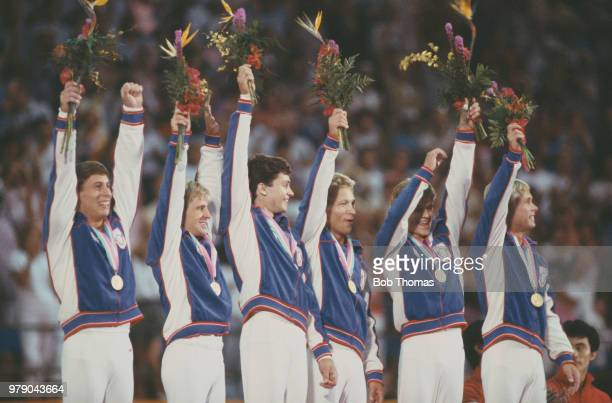 View of the United States men's gymnastics team celebrating on the medal podium after finishing in first place to win the gold medal in the Men's...