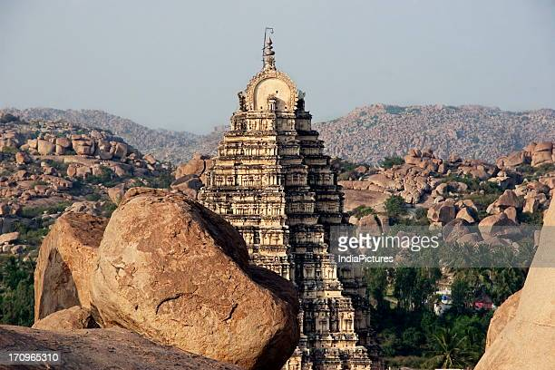 View of the upper portion of Virupaksha Temple amidst the giant boulders rocky mountains and vegetation Hampi Karnataka India