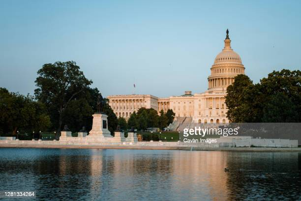 view of the us capitol building across reflecting pool - capitol hill stock pictures, royalty-free photos & images