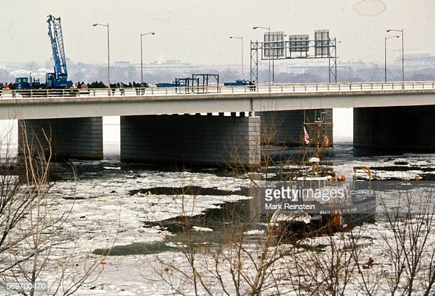 View of the US Coast Guard tugboat Capstan in the Potomac River and a large crane on a bridge to aid in the salvage of Air Florida Flight 90...