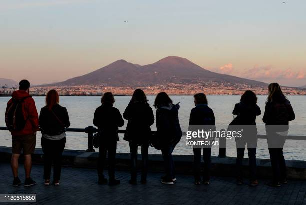 A view of the Vesuvius volcano seen from Naples at sunset with tourists taking pictures of the landscape