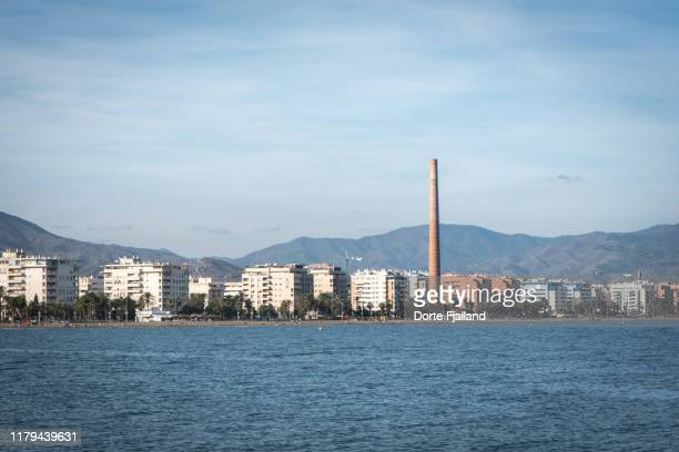 view of the western part of málaga from the sea with a tall chimney and apartment buildings along the coast. - dorte fjalland stock-fotos und bilder